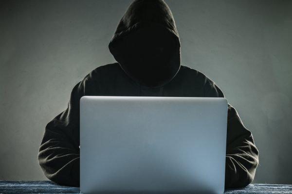 A hacker with a hood with laptop. Online network danger.